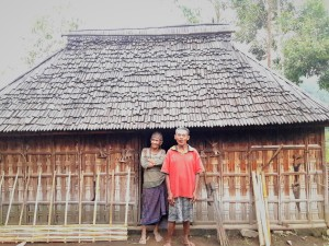 A one room bamboo home with the lovely couple standing in front.